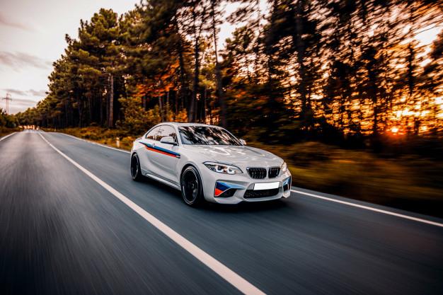 Hvid BMW kører i en skov