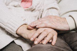 Et ældre par holder i hinandens hænder