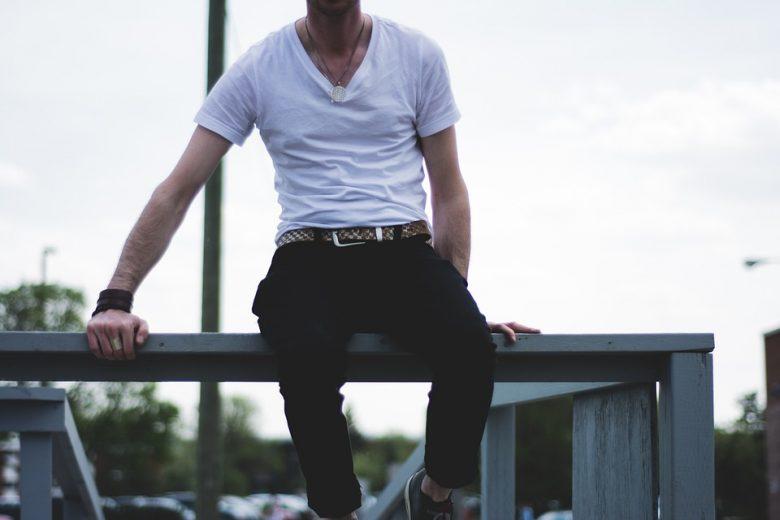 En mand med en hvis t-shirt sidder på et rækværk