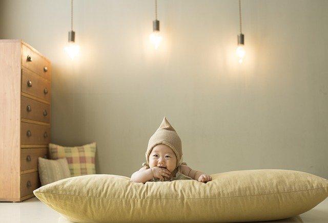Baby ligger ned på en stor pude og griner